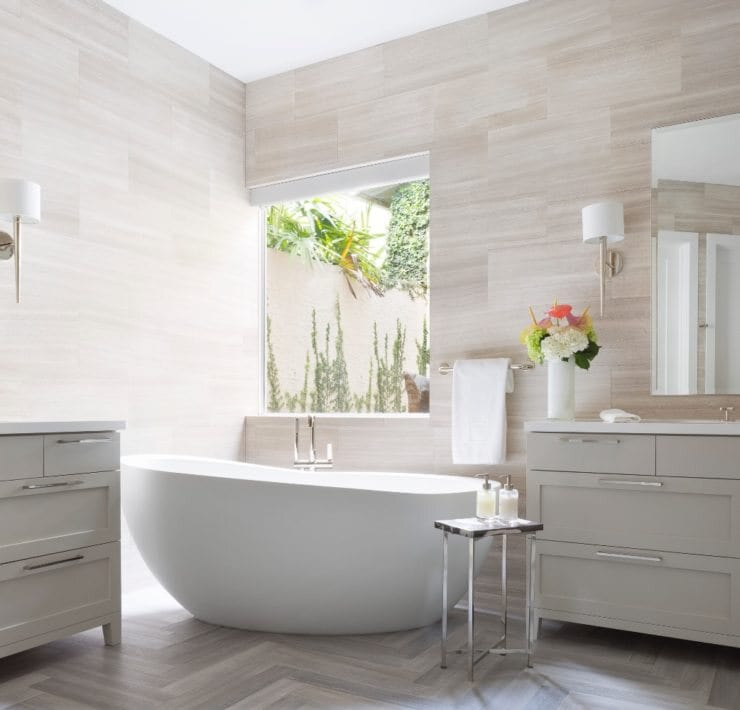 This master bathroom by Krista + Home features sconces by Kallista and hardware from Waterworks. Tile laid in a herringbone pattern is one of Watterworth Alterman's favorite applications to make the flooring pop.